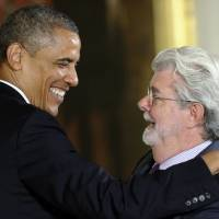 Photo - President Barack Obama hugs director George Lucas before presenting him with the 2012 National Medal of Arts, Wednesday, July 10, 2013, during a ceremony in the East Room of White House in Washington,. (AP Photo/Susan Walsh)