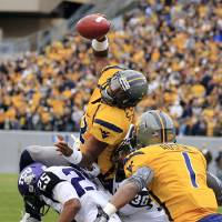 Photo -   West Virginia quarterback Geno Smith (12) is tackled at the goal line by TCU's Kevin White (25) and Joel Hasley (36) during the first half of their NCAA college football game in Morgantown, W.Va., on Saturday, Nov. 3, 2012. (AP Photo/Christopher Jackson)