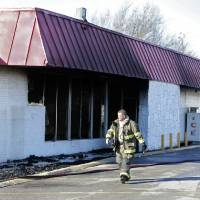 Photo - Below: A firefighter walks past the abandoned former grocery store in Tuttle that burned Thursday.