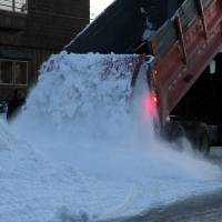Photo - A Nome public works truck dumps a load of snow onto Front Street on Sunday, March 9, 2014, in Nome, Alaska. The snow was trucked in to provide a trail for mushers to the finish line of the Iditarod Trail Sled Dog Race. (AP Photo/Mark Thiessen)
