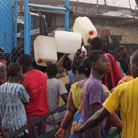 Photo - West Point residents try to buy water, rear, in one of the areas were the Ebola virus has claimed lives in Monrovia, Liberia, Thursday, Aug. 21, 2014. Calm returned Thursday to a slum in the Liberian capital that was sealed off in the government's attempt to halt the spread of Ebola, a day after clashes erupted between residents and security forces, but now the tens of thousands of residents are worried about getting food. (AP Photo/Abbas Dulleh)