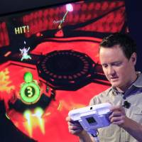 Photo -   Nintendo's Bill Trinen demonstrates the Wii U GamePad, Thursday, Sept. 13, 2012 in New York. The gaming console will start at $300 and go on sale in the U.S. on Nov. 18, in time for the holidays, the company said Thursday. (AP Photo/Mark Lennihan)