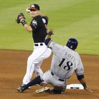 Photo - Miami Marlins second baseman Derek Dietrich, left, avoids a sliding Milwaukee Brewers' Khris Davis to turn a fifth-inning double play during a baseball game in Miami, Saturday, May 24, 2014. (AP Photo/Joe Skipper)