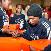 Photo - SHOE DONATION / DONATE: Player Kevin Durant autographs shoe boxes for students after they received new shoes. Players from the Oklahoma City Thunder NBA basketball team were joined by mascot, Rumble, and Thunder Girls in assisting children at Dunbar Elementary School  in trying on their new Nike athletic shoes donated by SandRidge employees Thursday, Dec. 17, 2009. Each player told the students their favorite holiday song.  Nick Collison: