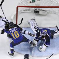 Photo -   Los Angeles Kings' Anze Kopitar, left, of Slovenia, scores past St. Louis Blues goalie Brian Elliott, right, and Blues' Andy McDonald (10) during the first period in Game 2 of an NHL second-round playoff series hockey game on Monday, April 30, 2012, in St. Louis. (AP Photo/Jeff Roberson)