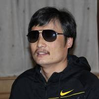 Photo -   In this photo taken in late April, 2012, and released by Zeng Jinyan, blind Chinese legal activist Chen Guangcheng is seen at an undisclosed location in Beijing during a meeting with human rights activists Hu Jia and Zeng Jinyan. Chen, an inspirational figure in China's rights movement, slipped away from his well-guarded rural village on April 22, 2012, and made it to a secret location in Beijing on Friday, April 27. Activists say Chen is under the protection of U.S. diplomats in Beijing. (AP Photo/Zeng Jinyan)