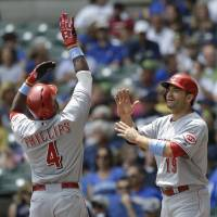 Photo - Cincinnati Reds' Brandon Phillips (4) gets a high-five from teammate Joey Votto after hitting a two-run home run during the first inning of a baseball game against the Milwaukee Brewers, Sunday, June 15, 2014, in Milwaukee. (AP Photo/Jeffrey Phelps)