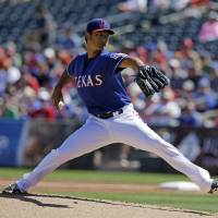 Photo - Texas Rangers starting pitcher Yu Darvish, of Japan, throws during the first inning of a spring exhibition baseball game Monday, March 10, 2014, in Suprise, Ariz. (AP Photo/Darron Cummings)