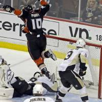 Photo - Anaheim Ducks right winger Corey Perry (10) leaps over Pittsburgh Penguins goalie Marc-Andre Fleury (29) as Perry scores a goal during the first period of an NHL hockey game in Anaheim, Calif., Friday, March 7, 2014. (AP Photo/Reed Saxon)