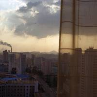 Photo - In this Aug. 7, 2012 photo, the sun sets over Pyongyang, North Korea, behind the curtained window of a downtown hotel room. (AP Photo/David Guttenfelder)