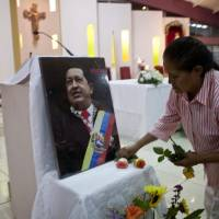 Photo - A woman places flowers in front of an image of Venezuela's President Hugo Chavez in preparation for a mass in support of him in Managua, Nicaragua, Wednesday Dec. 12, 2012. Venezuela's Information Minister Ernesto Villegas expressed hope about the Chavez's returning home for his Jan. 10 swearing-in for a new six-year term after his cancer surgery in Cuba, but said in a written message on a government website that if Chavez doesn't make it,