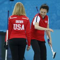 Photo - Team USA's Ann Swisshelm, right, pats skip Erika Brown on the behind after a good throw during a women's curling training session the 2014 Winter Olympics, Sunday, Feb. 9, 2014, in Sochi, Russia. (AP Photo/Robert F. Bukaty)