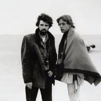 Photo -   In this March 1976 publicity photo released by Lucasfilm Ltd. & TM, director, George Lucas, and actor, Mark Hamill, who portrays young Luke Skywalker, are shown on the salt flats of Tunisia during principal photography of the original