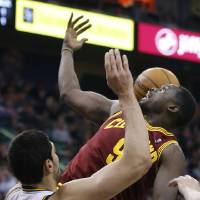 Photo - Cleveland Cavaliers Luol Deng, right, loses control of the ball as Utah Jazz's Enes Kanter defends during the first half of an NBA basketball game in Salt Lake City, Friday, Jan. 10, 2014. Cavaliers defeated the Jazz 113-102. (AP photo/George Frey)