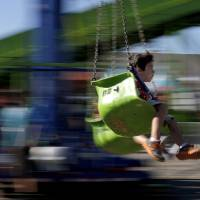 Photo - Nicholas Galvan, 6, of Yukon, Okla., rides a a swing ride during the last day of the Oklahoma State Fair in Oklahoma City, Sunday, Sept. 22, 2013. Photo by Sarah Phipps, The Oklahoman