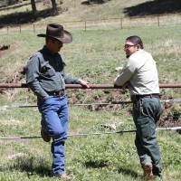 Photo - Otero cattle rancher association president Gary Stone talks to Lincoln National Forest District Ranger James Duran in Weed, New Mexico, Thursday, May 15, 2014. The Otero County Cattleman's Association is pitted against the National Forest Service over a fence intended to protect wildlife that the agency installed around a small creek where the ranchers' cattle drink water. (AP Photo/Juan Carlos Llorca)