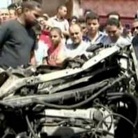 Photo - In this image made from pool video provided by APTN, Libyan men inspect a destroyed car at the scene of a car bomb explosion in Benghazi, Libya, Monday, May 13, 2013. A car bomb exploded Monday near a hospital in the eastern Libyan city of Benghazi, killing many, officials said, in one of the biggest attacks since the end of the civil war that ousted former dictator Moammar Gadhafi. (AP Photo/APTN, Al Ahrar)