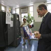 Photo - Democratic comptroller hopeful Eliot Spitzer waits his turn to cast his vote in the primary election at his polling station in New York, Tuesday, Sept. 10, 2013.  (AP Photo/Mary Altaffer)
