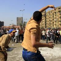 Photo -   A protester throws a stone after scuffles broke out between groups of several hundred protesters in Tahrir square when chants against the new Islamist president angered some in the crowd in Cairo, Egypt, Oct. 12, 2012. The scuffles between supporters and opponents of President Mohammed Morsi reflect deep political divisions among the country's 82 million people, more than a year after the popular uprising that toppled Hosni Mubarak. (AP Photo/Khalil Hamra)