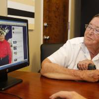 Photo - Madelynn Taylor, 74, looks at a 2011 photo of herself (in red) with her wife Jean Mixner, in Boise, Idaho on July 7, 2014.  Taylor has filed a lawsuit seeking the right to have her deceased wife interred with her at the Idaho State Veterans Cemetery. Idaho state law allows only married couples who are legally recognized by the state to be buried together at the cemetery; the state has refused to recognize Taylor's legal marriage to Mixner in California as valid. (AP Photo/Otto Kitsinger)