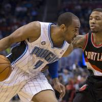 Photo - Orlando Magic's Arron Afflalo (4) takes the ball inside the key against Portland Trail Blazers' Damian Lillard (0) during the first half of an NBA basketball game in Orlando, Fla., Tuesday, March 25, 2014. (AP Photo/Willie J. Allen Jr.)