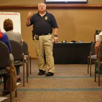 Photo - Police Sgt. Bob Moore talks to a group of women taking a