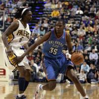 Photo - Oklahoma City Thunder guard Kevin Durant, right, drives on Indiana Pacers guard Marquis Daniels in the first half of an NBA basketball game in Indianapolis, Monday, Nov. 10, 2008. (AP Photo/Michael Conroy) ORG XMIT: NAF102