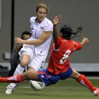 Photo - FILE - In this Jan. 27, 2012, file photo, United States' Kelly O'Hara (5) fights for control of the ball with Costa Rica's Daniela Cruz (8) during the first half of CONCACAF women's Olympic qualifying soccer game action at B.C. Place in Vancouver, British Columbia. A group of players from the U.S. women's national team, who will vie for a spot in the World Cup in October qualifying, have joined with several international players in protesting the turf surfaces for next summer's big event in Canada. (AP Photo/The Canadian Press, Jonathan Hayward, File)