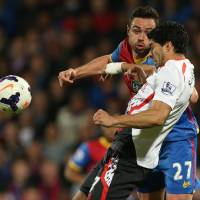 Photo - Crystal Palace's Damien Delaney, background,  challenges Liverpool's Luis Suarez during the English Premier League soccer match between Crystal Palace and Liverpool at Selhurst Park stadium in London, Monday, May 5, 2014. (AP Photo/Alastair Grant)