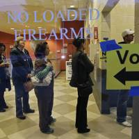 Photo -   Behind a sign barring loaded firearms in the building, people stand in line to cast their votes on Election Day as the polls opened at a precinct at the Wake County Firearms Education and Training Center in Apex, N.C., Tuesday, Nov. 6, 2012. (AP Photo/Gerry Broome)