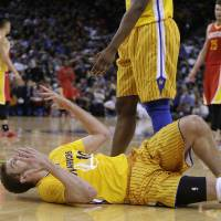 Photo - Golden State Warriors' David Lee (10) gestures from the floor after being called for a foul during the second half of an NBA basketball game against the Houston Rockets Friday, March 8, 2013, in Oakland, Calif. The Rockets won 94-88. (AP Photo/Ben Margot)