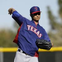 Photo - FILE - In this Feb. 17, 2014 file photo, Texas Rangers' Yu Darvish throws as he participates in fielding drills during spring training baseball practice in Surprise, Ariz. Darvish has been scratched from his scheduled start in Monday's, April 31, 2014 season opener because of stiffness in his neck.  The announcement Tuesday came a day after Darvish stopped throwing while playing catch. (AP Photo/Tony Gutierrez, File)