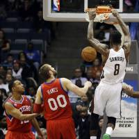 Photo - Milwaukee Bucks' Larry Sanders (8) dunks in front of Philadelphia 76ers' Evan Turner, left, and Spencer Hawes (00) during the first half of an NBA basketball game, Tuesday, Jan. 22, 2013, in Milwaukee. (AP Photo/Jeffrey Phelps)