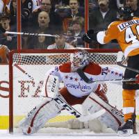 Photo - Philadelphia Flyers' Vincent Lecavalier, right, tries to knock the puck past Washington Capitals' Braden Holtby during the first period of an NHL hockey game, Wednesday, March 5, 2014, in Philadelphia. (AP Photo/Matt Slocum)