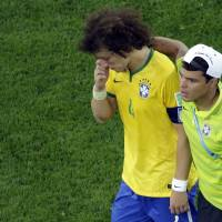 Photo - Brazil's David Luiz is consoled by teammate Thiago Silva as they walk off the pitch after the World Cup semifinal soccer match between Brazil and Germany at the Mineirao Stadium in Belo Horizonte, Brazil, Tuesday, July 8, 2014. Germany has routed host Brazil 7-1 and advanced to the final of the World Cup. (AP Photo/Felipe Dana, Pool)