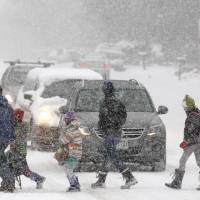 Photo - Elementary school students, some escorted by parents, cross a snowy street en route to school as a blizzard dropped snow over Boulder, Colo., Wednesday Dec. 19, 2012. A storm that has dumped more than a foot of snow in the Rocky Mountains is heading east and is forecast to bring the first major winter storm of the season to the central plains and Midwest. (AP Photo/Brennan Linsley)