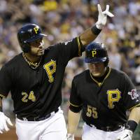 Photo - FILE - In this July 3, 2013 file photo, Pittsburgh Pirates' Pedro Alvarez (24) celebrates as he returns to the dugout with teammate Pirates' Russell Martin (55), who scored on his three-run home run off Philadelphia Phillies starting pitcher John Lannan during the fifth inning of a baseball game in Pittsburgh. Much of the focus as baseball heads into the second half is being placed on the possible suspensions of Alex Rodriguez, Ryan Braun and a handful of All-Stars implicated in the Biogenesis performance-enhancing drug scandal. Puigmania, a Pirates revival and one impressive power show in Baltimore should shift the gaze right back onto the field. (AP Photo/Gene J. Puskar, File)