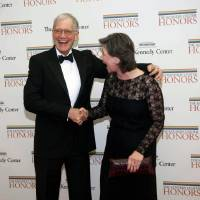 Photo - 2012 Kennedy Center Honoree comedian David Letterman shakes hands with his wife Regina as they arrive at the State Department for the Kennedy Center Honors Gala Dinner on Saturday, Dec. 1, 2012 in Washington. (AP Photo/Kevin Wolf)