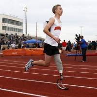 Photo - Norman's Patrick Ahearn runs the 400-meter dash with his prosthetic leg during a track meet at Putnam City High School in Oklahoma City, Friday, April 5, 2013. Ahearn lost part of his leg in a personal watercraft accident last year. Photo by Nate Billings, The Oklahoman