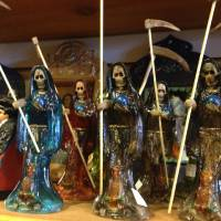 Photo - in this Feb. 13, 2013 photo, statues of La Santa Muerte are shown at the Masks y Mas art store in Albuquerque, N.M. La Santa Muerte, an underworld saint most recently associated with the violent drug trade in Mexico, now is spreading throughout the U.S. among a new group of followers ranging from immigrant small business owners to artists and gay activists. In addition to showing up at drug crime scenes, the once-underground icon has been spotted on passion candles in Richmond, Va. grocery stores. The folk saint's image can be seen inside New York City apartments, in Minneapolis religious shops and during art shows in Tucson, Ariz.  (AP Photo/Russell Contreras)