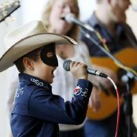 Photo -  Maddox Ross, 9, sings as he wears a Lone Ranger mask during the 2013 National Day of the American Cowboy at the National Cowboy & Western Heritage Museum in Oklahoma City. Photo by Nate Billings, The Oklahoman Archives