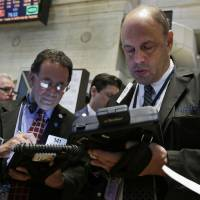 Photo - Randy Beller, right, works with fellow traders on the floor of the New York Stock Exchange Thursday, April 24, 2014. Mixed earnings from a large number of U.S. companies left the stock market without direction early Thursday, despite positive results from a handful of names including Apple and Caterpillar. (AP Photo/Richard Drew)