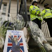 Photo - A card is left on a floral tribute outside former British Prime Minister Baroness Thatcher's home in London, Tuesday, April 9, 2013. Margaret Thatcher, the combative