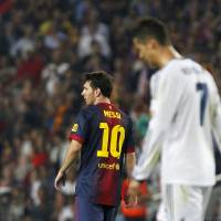 Photo -   Real Madrid's Cristiano Ronaldo from Portugal, right, and FC Barcelona's Lionel Messi from Argentina, left, gesture during a Spanish La Liga soccer match at the Camp Nou stadium in Barcelona, Spain, Sunday, Oct. 7, 2012. (AP Photo/Andres Kudacki)