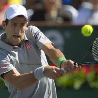 Photo - Novak Djokovic, of Serbia, hits to Julien Benneteau, of France, in their quarterfinal match at the BNP Paribas Open tennis tournament on Friday, March 14, 2014, in Indian Wells, Calif. (AP Photo/Mark J. Terrill)