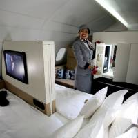 "Photo - An Etihad Airways official stands inside the 125-square-foot (11.61-square-meter) area that includes a ""living room"" partitioned off from the first-class aisle, leather seating, a chilled minibar and a 32-inch flat-screen TV, at a training facility in Abu Dhabi, United Arab Emirates, Sunday, May 4, 2014. Etihad Airways, a fast-growing Mideast carrier, laid out plans Sunday to offer passengers who find first-class seats a bit too tight a miniature suite featuring a closed-off bedroom, private bathroom and a dedicated butler. (AP Photo/Kamran Jebreili)"