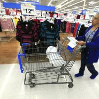 Photo - TRIAD volunteer Maxine Washington shops for Christmas presents at a local Wal-Mart store as local law enforcement, in partnership with Sunbeam Family Services, select gifts for the Grandparents Raising Grandchildren Program in Oklahoma City.Grandchildren Program is offered through Sunbeam's Caregiver Fundamentals Program for grandparents who are raising their grandchildren.  PAUL B. SOUTHERLAND - PAUL B. SOUTHERLAND