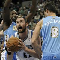 Photo -   Minnesota Timberwolves' Kevin Love, center, eyes the basket between Denver Nuggets' Danilo Gallinari, right, of Italy, and another defender in the first half of an NBA basketball game on Wednesday, Nov. 21, 2012, in St. Paul. it was Love's return to the lineup for the first time in regular season play after suffering a broken hand. (AP Photo/Jim Mone)
