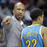 Photo - New Orleans Hornets coach Monty Williams, left, talks to Brian Roberts during the first half of an NBA basketball game against the Memphis Grizzlies in Memphis, Tenn., Sunday, Jan. 27, 2013. (AP Photo/Danny Johnston)