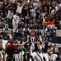 Photo -   The Chicago Bears bench celebrates as outside linebacker Lance Briggs (55) returns an interception from Dallas Cowboys quarterback Tony Romo for a touchdown during the second half of an NFL football game, Monday, Oct. 1, 2012, in Arlington, Texas. (AP Photo/LM Otero)